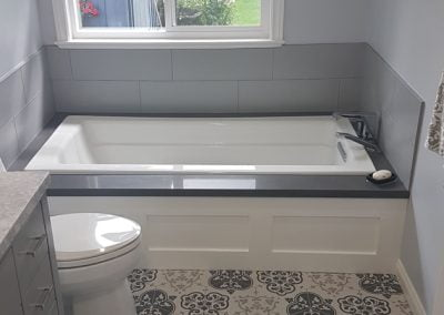 Built-in tub with Quartz surround tub lip, custom wainscoting and art décor tiles