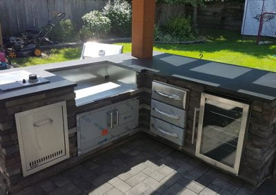 Custom outdoor BBQ kitchen with ledgestone and quartz countertops