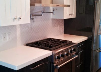 Herringbone patterned backsplash with new double tone cabinets and pot filler behind the stove.