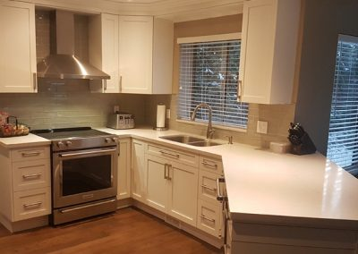 Full Kitchen Renovation with white shaker cabinets and white quartz countertops. Boxes are plywood boxes with soft close hinges and stainless steel appliances