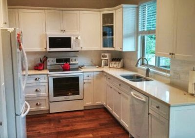 White Shaker Kitchen with white subway tile backsplash and white quartz countertops
